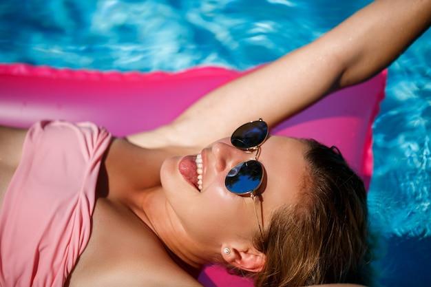 Modelo de mulher em óculos de sol, descansando e tomando banho de sol em um colchão na piscina. mulher em um maiô de biquíni rosa flutuando sobre um colchão inflável rosa. fps e protetor solar