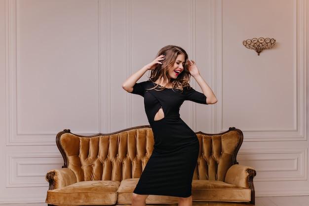 Modelo de mulher engraçada, bonita e esguia se divertindo ouvindo sua música favorita, posando com os olhos fechados e sorrindo sinceramente na sala branca com um lindo sofá macio