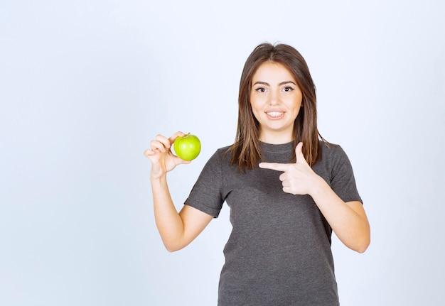 Modelo de mulher jovem apontando para uma maçã verde.