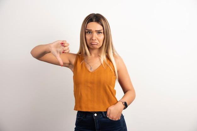 Modelo de mulher jovem com roupas casuais, mostrando o polegar para baixo e posando
