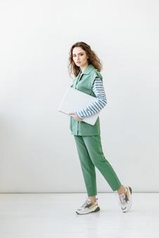 Modelo de mulher jovem dando passos dentro de casa segurando o laptop nas mãos em cena branca