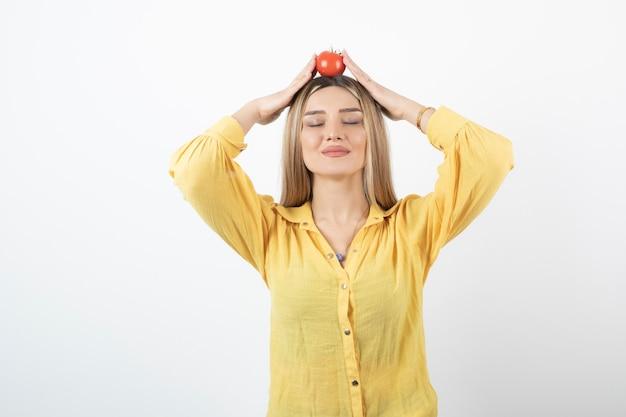 Modelo de mulher jovem e atraente em pé e segurando uma sobrecarga de tomate vermelho.