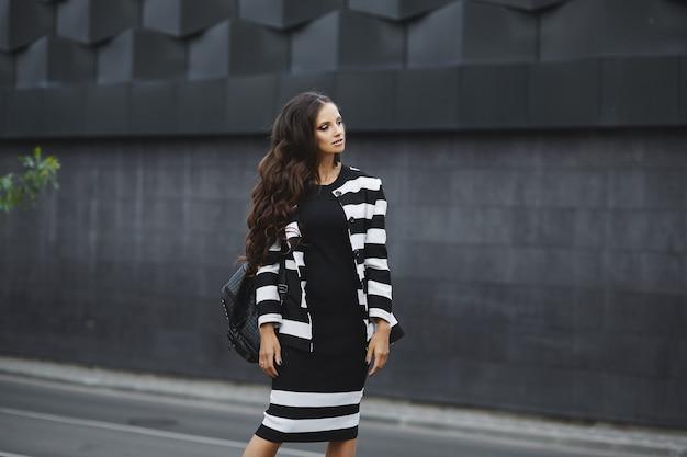 Modelo de mulher jovem e bonita com uma bolsa em uma jaqueta elegante e vestido, caminhando ao ar livre na cidade yo ...