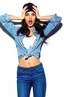 Modelo de mulher jovem e bonita elegante de look.glamor de alta moda com lábios vermelhos no pano de hipster jeans colorido brilhante de verão no gorro preto