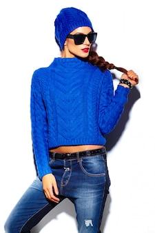 Modelo de mulher jovem e bonita elegante glamour com lábios vermelhos em pano de hipster suéter azul no gorro