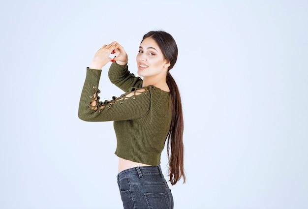Modelo de mulher jovem e bonita fazendo a forma do símbolo do coração com as mãos.