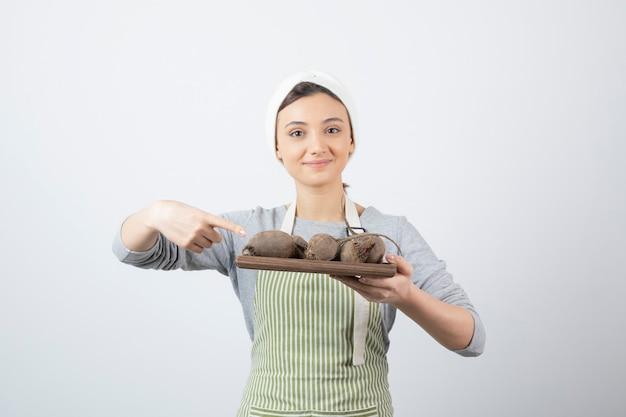 Modelo de mulher jovem e bonita no avental, apontando para uma placa de madeira com beterraba.
