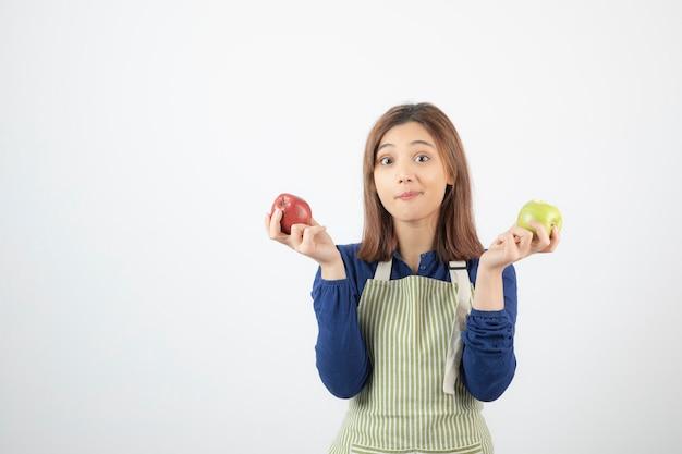 Modelo de mulher jovem e bonita no avental segurando maçãs.
