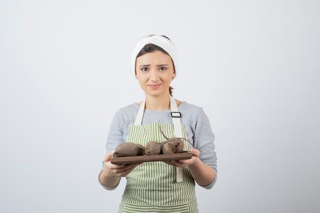 Modelo de mulher jovem e bonita no avental segurando uma placa de madeira com beterraba.