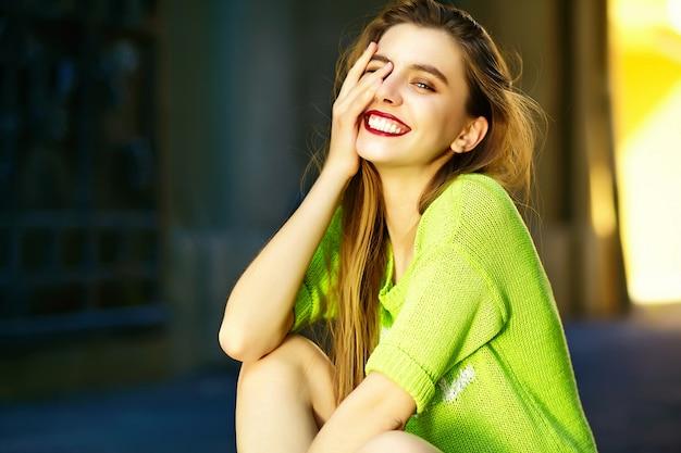 Modelo de mulher jovem e bonita sexy elegante engraçado sorridente no pano de hipster amarelo brilhante de verão sentado na rua