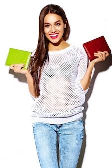 Modelo de mulher jovem e bonita sorridente sexy elegante à moda de alta moda no pano casual branco brilhante de verão com bolsa de embreagem colorida