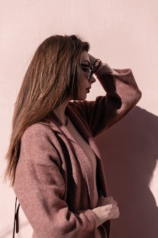 Modelo de mulher jovem e muito atraente com casaco elegante em óculos de sol da moda poses perto de parede rosa vintage em dia ensolarado. menina moderna com roupas lindas toca o cabelo e aproveita a luz do sol ao ar livre.