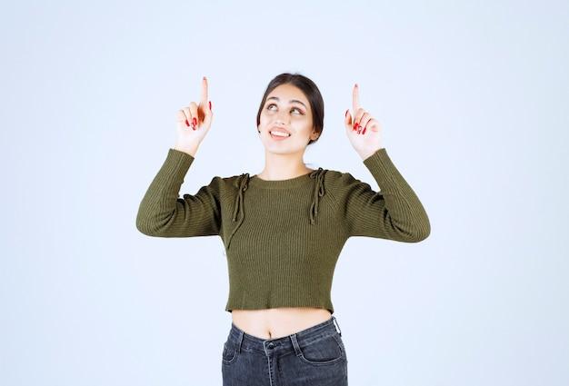Modelo de mulher jovem em pé e apontando para cima com os dedos indicadores.
