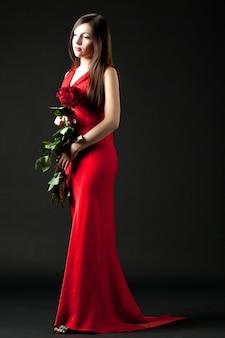 Modelo de mulher jovem morena com vestido longo de noite vermelho em pé e segurando buquê de rosas vermelhas nas mãos sobre um fundo escuro no estúdio fotográfico