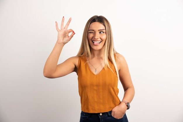 Modelo de mulher jovem mostrando gesto ok e posando.