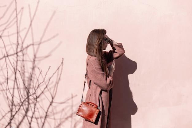 Modelo de mulher jovem muito elegante com cabelo comprido, em um elegante casaco com bolsa de couro em óculos de sol se passando perto de uma parede rosa vintage em um dia ensolarado. modelo de moda menina elegante posando no sol.