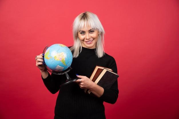 Modelo de mulher jovem posando com livros e um globo terrestre em uma parede vermelha.