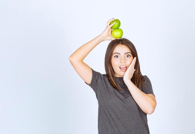 Modelo de mulher jovem segurando duas maçãs verdes no alto