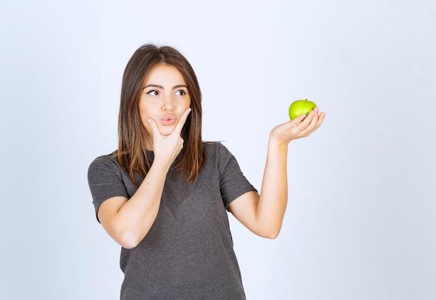 Modelo de mulher jovem segurando uma maçã verde.