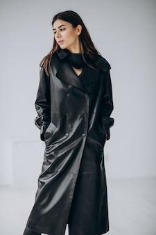 Modelo de mulher jovem, vestindo casaco de couro preto longo