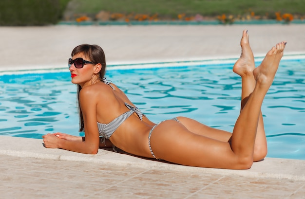 Modelo de mulher linda e sexy de biquíni relaxando na piscina
