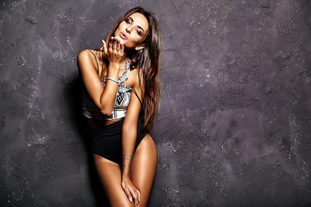 Modelo de mulher linda tomando banho de sol em roupas de verão com maquiagem criativa brilhante posando perto da parede cinza