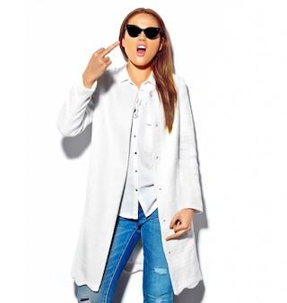 Modelo de mulher morena bonita com roupas de verão casual hipster isolado no branco em óculos de sol mostrando a foda do sinal