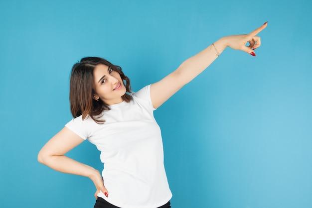 Modelo de mulher morena em pé e apontando para a parede azul