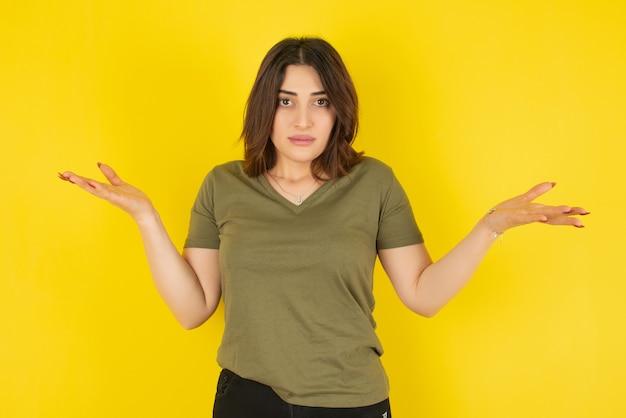 Modelo de mulher morena em pé e encolhendo os ombros contra a parede amarela