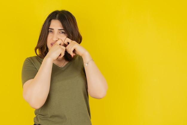 Modelo de mulher morena em pé e posando contra a parede amarela