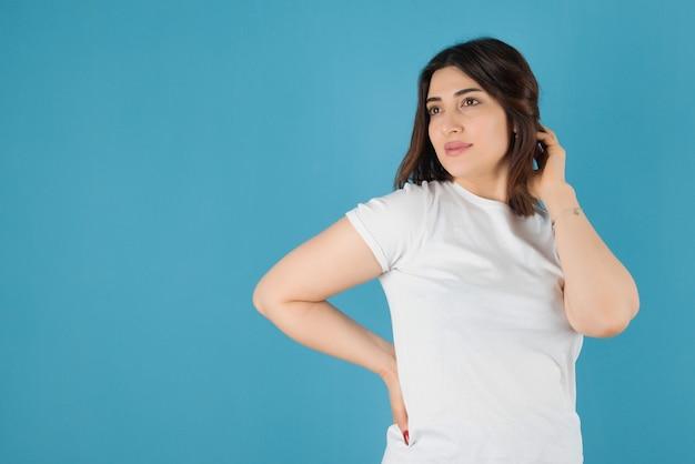 Modelo de mulher morena em pé e posando contra uma parede azul