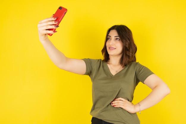 Modelo de mulher morena em pé e tirando selfie com o celular contra a parede amarela