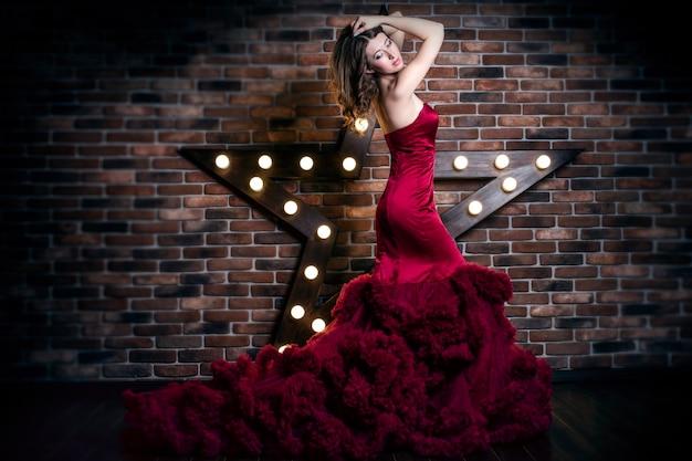 Modelo de mulher morena linda com vestido vermelho luxuoso com maquiagem