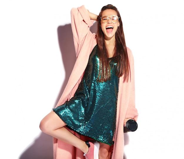 Modelo de mulher morena sorridente hipster bonito no sobretudo rosa elegante. bebendo café