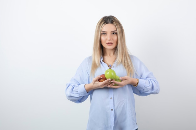 Modelo de mulher muito atraente em pé e segurando maçãs frescas.