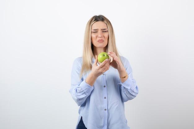 Modelo de mulher muito atraente em pé e segurando uma maçã verde fresca.