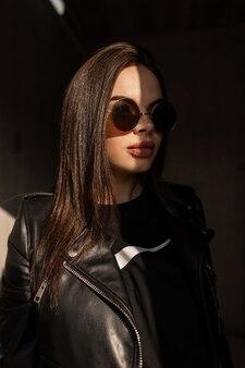 Modelo de mulher na moda hippie em roupas pretas elegantes, com jaqueta e óculos de sol vintage redondos fica na luz do sol e na sombra em um fundo escuro. retrato feminino criativo