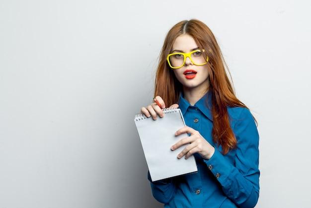 Modelo de mulher posando com óculos em uma parede de luz, emoções com um notebook nas mãos dela