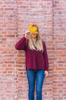 Modelo de mulher sem rosto olhando embora outono folha Foto gratuita