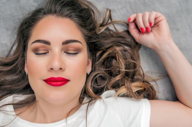Modelo de mulher sensual com cabelo castanho voador varrido pelo vento em fundo cinza claro. penteado brilhante e de longa saúde. beleza e cuidados com o cabelo. maquiagem de moda natural