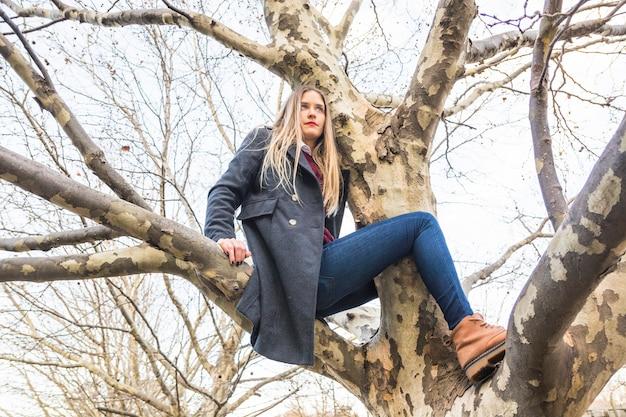 Modelo de mulher sentada no galho de árvore
