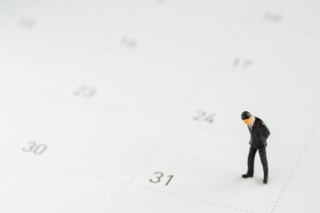 Modelo de negócio de miniture em pé e olhando para a data de número 31. final do dia para pagamento de salários e outras despesas.