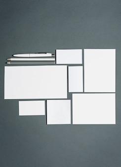 Modelo de negócios com cartões, papéis, caneta. espaço cinza.