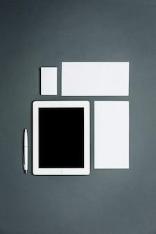 Modelo de negócios com cartões, papéis, tablet. espaço cinza.