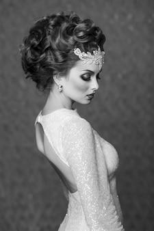 Modelo de noiva virado com as costas com penteado de alta costura e acessórios de noiva, preto e branco