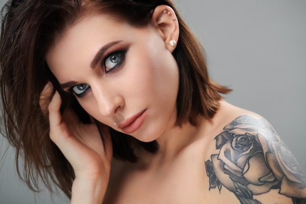 Modelo de olho esfumaçado com tatuagem de rosa no ombro