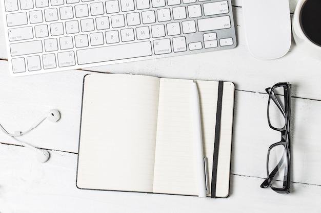 Modelo de papelada em branco para designers. mapeamento de design responsivo no fundo de madeira vintage. papel, cabeçalho, xícara de café, smartphone, lápis e fones de ouvido no fundo da mesa de madeira. vista do topo.