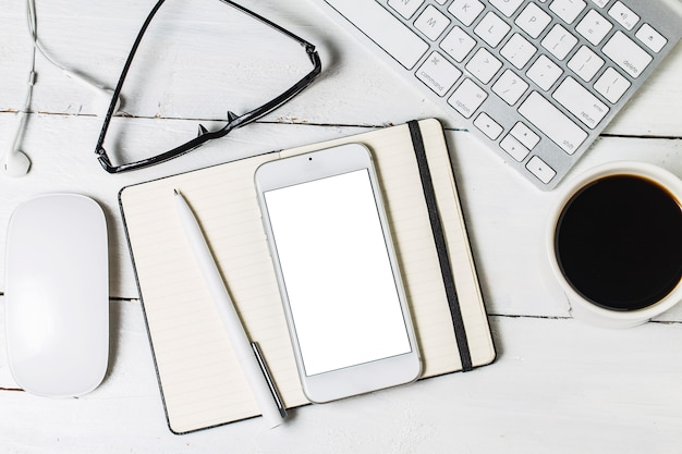 Modelo de papelada em branco para designers. maquete de design responsivo em fundo de madeira vintage. papel, cabeçalho, xícara de café, smartphone, lápis e fones de ouvido no fundo da mesa de madeira. vista do topo.