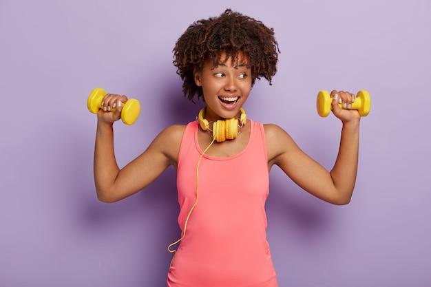 Modelo de pele escura satisfeita com cabelo encaracolado, vestida com uma camisa casual rosa, levanta os braços com halteres, treina músculos, ouve música com fones de ouvido