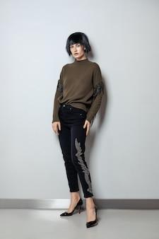 Modelo de peruca preta, pulôver com franja e jeans com strass